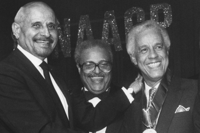 L. Douglas Wilder (R) beams upon receiving the 75th NAACP Spingarn Medal from former recipient Percy Ellis Sutten (L) of New York on July 12, 1990, in Los Angeles. On Jan. 13, 1990, Wilder took office in Virginia, becoming the first elected African-American governor of a U.S. state. File Photo by Jim Ruymen/UPI