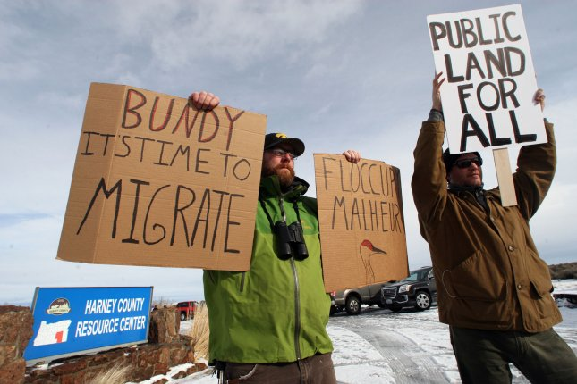 Biologists Cody Martz, left, and Taylor McKinnon hold protest signs at the Malheur National Wildlife Reserve on January 16 in Burns, Ore. Ammon Bundy and about 20 other protesters took over the refuge on Jan. 2 after a rally to support the imprisoned local ranchers Dwight Hammond Jr., and his son, Steven Hammond. Photo by Jim Bryant/UPI