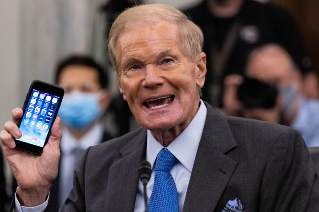 Bill Nelson, the NASA administrator nominee, holds up a cellphone as an example of technology that NASA missions helped advance, during his confirmation hearing Wednesday before the Senate Committee on Commerce, Science and Transportation on Capitol Hill in Washington, D.C. Pool photo by Graeme Jennings/UPI