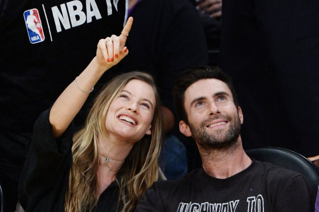 Adam Levine (R) and wife Behati Prinsloo at Kobe Bryant's final game with the Los Angeles Lakers on April 13. The couple are expecting their first child. File Photo by Jim Ruymen/UPI
