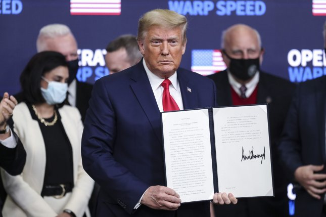 President Donald Trump signs an executive order giving priority to Americans to receive U.S.-made coronavirus vaccines Tuesday. Photo by Oliver Contreras/UPI