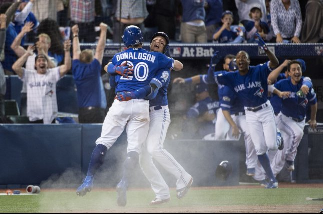Toronto Blue Jays' Josh Donaldson, left, and Troy Tulowitzki celebrate Donaldson scoring the game-winning run in extra innings of Game 3 of the ALDS against the Texas Rangers at the Rogers Centre in Toronto, Canada on October 9, 2016. Photo by Darren Calabrese/UPI