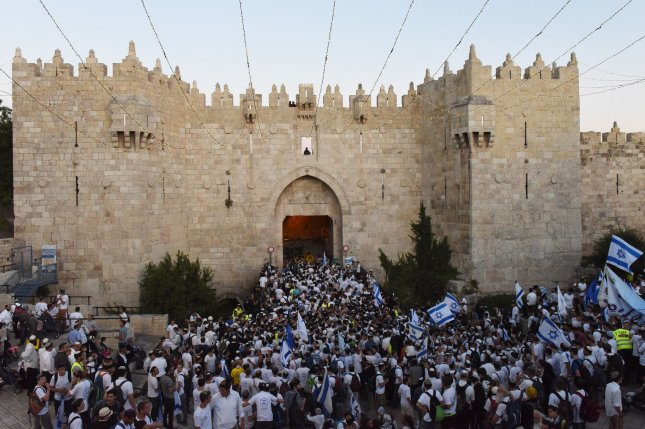 Right-wing Israelis wave national flags as they enter the Damascus Gate leading to the Muslim Quarter of the Old City of Jerusalem, May 24, on Jerusalem Day commemorating Israel's victory in the Six-Day War in 1967. Israel is celebrating the 50th anniversary of it's control over Jerusalem. Photo by Debbie Hill/UPI