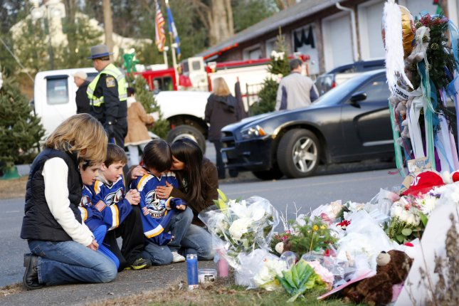 Mourners gather near a memorial filled with flowers, stuffed toys and candles at the entrance to Sandy Hook Elementary School in Newtown, Conn., following a shooting December 14, 2012. File Photo by John Angelillo/UPI