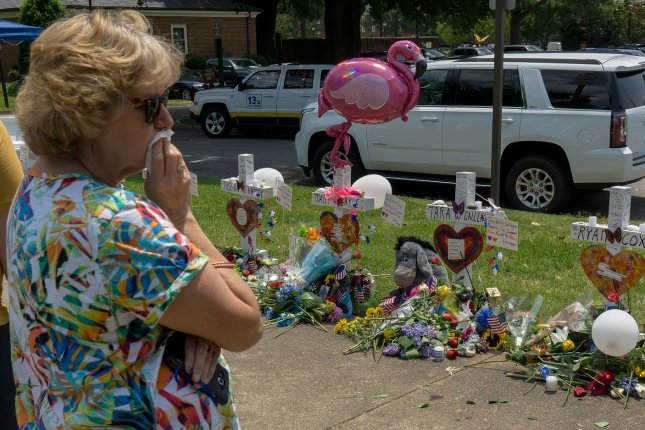 A woman becomes emotional as she visits an impromptu memorial outside a police station near the scene of a mass shooting where 12 people were killed, in Virginia Beach, Va. Friday. On Tuesday, Gov. Ralph Northam called a special session to address gun control. Photo by Ray Stubblebine/UPI