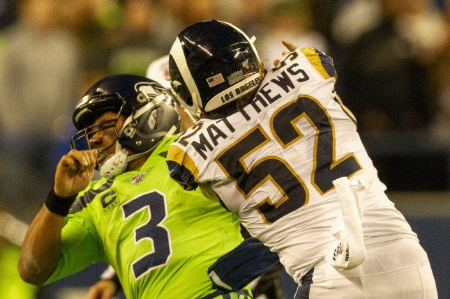 Los Angeles Rams outside linebacker Clay Matthews (52) pushes Seattle Seahawks quarterback Russell Wilson (3) and gets a roughing the passer penalty that kept the winning drive alive during the fourth quarter Thursday at CenturyLink Field in Seattle, Washington. Photo by Jim Bryant/UPI