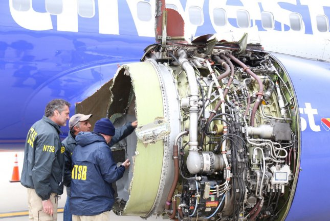 Investigators with the National Transportation Safety Board examine damage to a Southwest Airlines Boeing 737 that was forced to land in Philadelphia on April 17, 2018. File Photo by NTSB/UPI