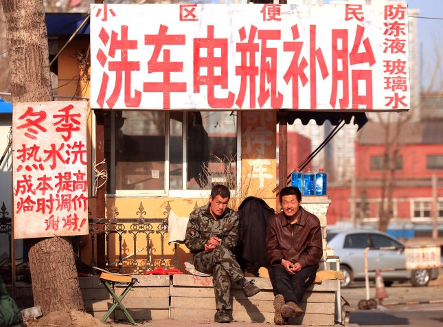 Chinese workers wait for customers at their roadside carwash in downtown Beijing January 9, 2012. China is raising minimum wages in some key provinces as local officials try to combat labour shortages and growing worker unrest. UPI/Stephen Shaver
