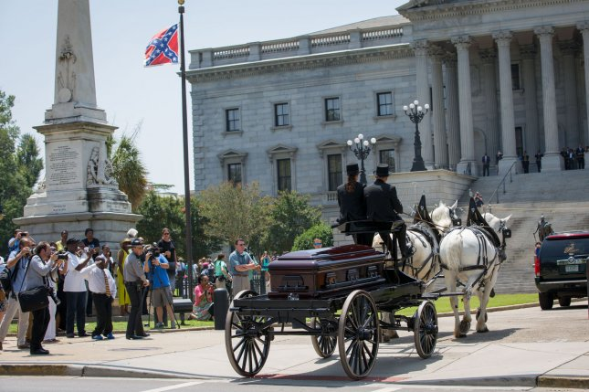 With the Confederate battle flag in the background, South Carolina state Sen. Clementa Pinckney's remains arrive by horse drawn carriage Wednesday at the South Carolina State House in Columbia, S.C. Photo by Kevin Liles/UPI