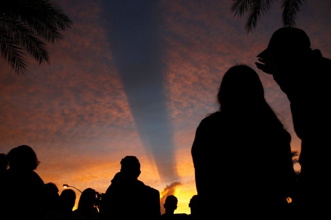 Mourners view a colorful sunset with a unique shadow that extends over the 'Healing Gardens' memorial Monday on the one-year anniversary of the shooting attack in Las Vegas, Nevada. Photo by James Atoa/UPI
