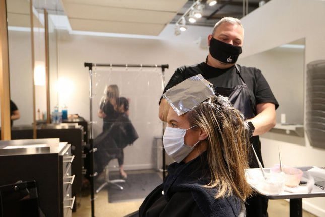 Stylist Jason Owen adds color to the hair of customer Susan Berardi while practicing safety with plastic sheeting at Dominic Michael Salon in Clayton, Missouri, on May 18, 2020. Photo by Bill Greenblatt/UPI