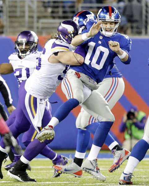 Minnesota Vikings defensive end Brian Robison hits New York Giants quarterback Eli Manning after Manning releases a pass during a game in 2013. File photo by John Angelillo/UPI