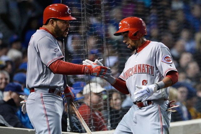 Cincinnati Reds' Eugenio Suarez (L) high fives teammate Billy Hamilton after Hamilton hit a solo home run during the first inning against the Chicago Cubs of the Cubs home opener at Wrigley Field in Chicago on April 11, 2016. Photo by Brian Kersey/UPI