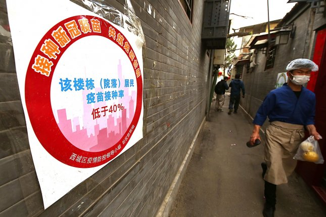 A Chinese cook walks past a housing community with a sign indicating a 40% vaccination rate of residents in Beijing on Sunday. China's capital is color-coding some businesses and housing areas to show the proportion of employees and residents vaccinated. Photo by Stephen Shaver/UPI