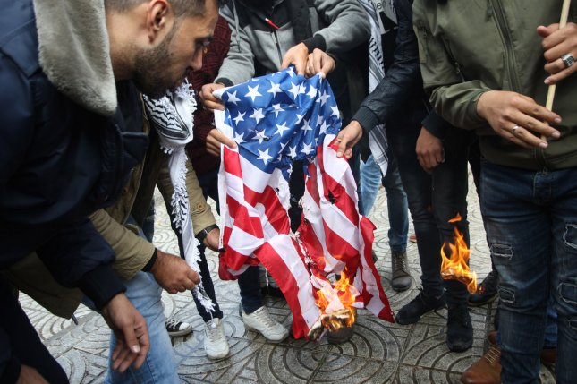 Palestinian protesters burn the US flag during a protest against US President Donald Trump in Gaza City on Wednesday. Photo by Ismael Mohamad/ UPI
