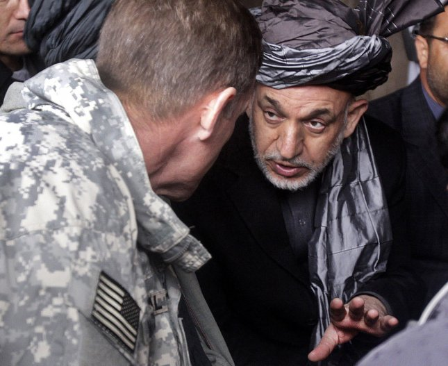 Hamid Karzai, president of the Islamic Republic of Afghanistan, speaks with Gen. Stanley A. McCrystal, commander of NATO International Security Assistance Force and US Forces Afghanistan, at a local store in Nawa district's marketplace on January 2, 2010. The pair was also joined by Mohammed G. Mangal, governor of Helmand province, to see progress in Nawa and meet with the district council, citizens and US Marines. UPI/Brian Tuthill/DOD