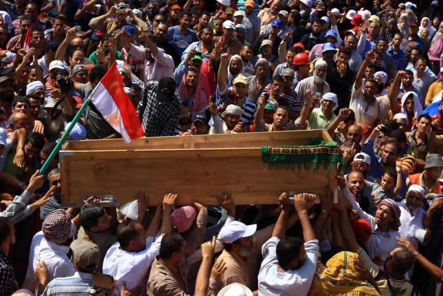 Supporters of Mohamed Morsi chanting slogans while carrying the coffin of the body of Egyptian killed in clashes with Egyptian security forces, near the Rabaah al-Adawiya mosque in the Nasr City neighborhood of Cairo, July 27, 2013. (UPI/Ahmed Jomaa)