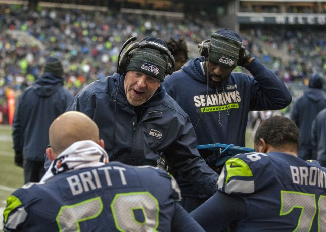 Seattle Seahawks offensive tackle Duane Brown (R) listens to instruction from offensive line coach Tom Cable while sitting next to center Justin Britt during a game against the Washington Redskins in November. Photo by Jim Bryant/UPI