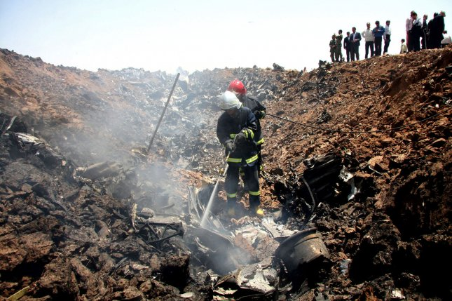 Iranian firefighters search at the site where a Russian-made Tupolev plane crashed near the city of Qazvin, about 93 miles north of Tehran, Iran, on July 15, 2009. File Photo by Erfan Dadkhah/IRNA