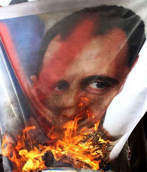 Syrian protestors burn pictures of Syrian President Bashar al-Assad in front of of the Arab League headquarters during the Arab League emergency session on Syria at the Arab League headquarters in Cairo, Egypt, November12, 2011. The Arab League has voted to suspend Syria from all meetings until it implements plan to end bloodshed in the civil protests. UPI/ Ahmed Ahmed