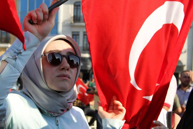 A veiled woman holds a Turkish flag during a demonstration in Istanbul in support the government on Saturday following a failed coup attempt. Turkey's Ministry of Education has suspended more than 15,000 education staff on accusations of having links to a cleric living in the United States who the Turkish government alleges organized a recent coup d'etat attempt. Photo by Hanna Noori/ UPI