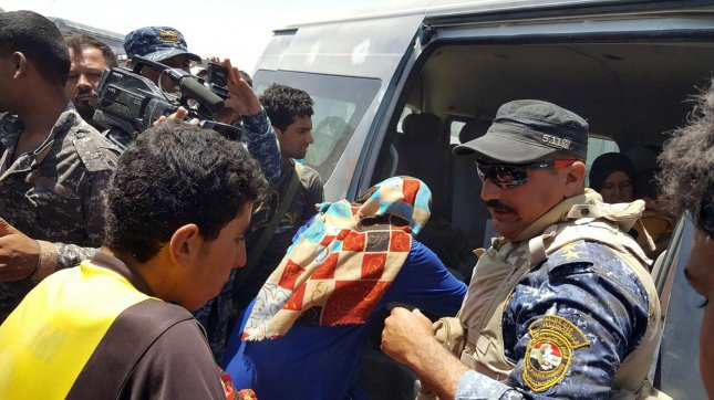 Members of the Iraqi security forces assist civilians, who fled their homes in and around Fallujah due to fighting between Iraqi government forces and the Islamic State, south of Fallujah, Iraq, on Wednesday. Photo by Abbas Mohammed /UPI