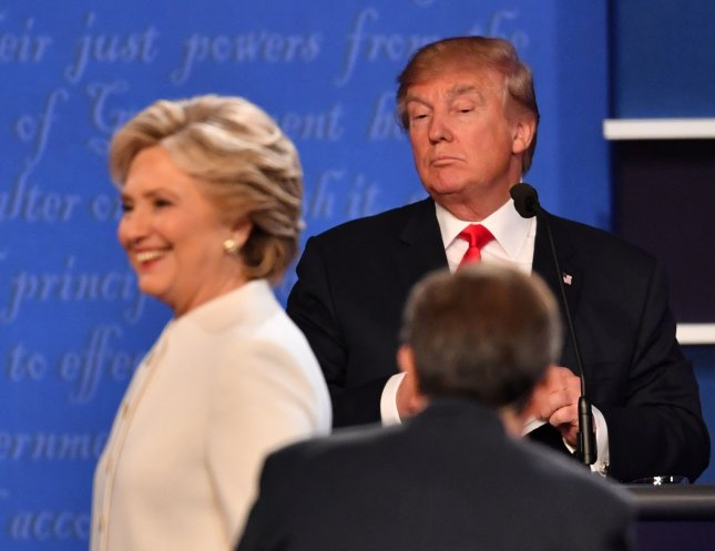 Democratic presidential candidate Hillary Clinton smiles as she walks between moderator Chris Wallace and Republican presidential candidate Donald Trump following their debate at the University of Nevada, Las Vegas, Wednesday night. It was the final debate before election day. Photo by Kevin Dietsch/UPI
