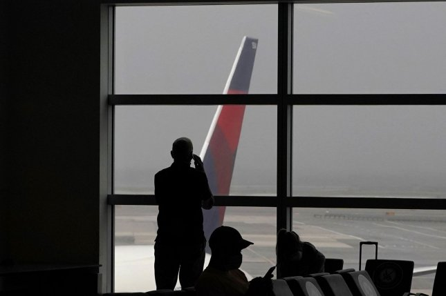 Passengers look at a Delta Air Lines flight outside of Terminal 4 at John F. Kennedy International Airport in New York City on August 4. File Photo by John Angelillo/UPI