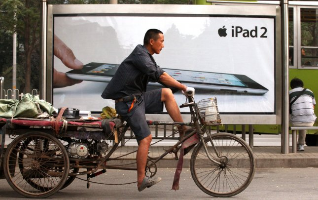 A Chinese worker rides past a sidewalk billboard advertising Apple's new iPad 2 now on sale in Beijing on July 5, 2011. Despite the iPad 2 clone invasion in China's big cities, the real iPad 2 remains extremely popular in China. Apple is planning to open its fifth store in the country by the end of the year. Chinese vendors are reportedly purchasing iPad displays rejected by Apple to use in iPad clones. UPI/Stephen Shaver