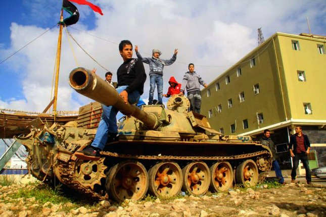 Libyans stand atop an army tank in the eastern dissident-held city of Benghazi on February 26, 2011. U.S. President Barack Obama urged Libyan leader Moammar Gadhafi to leave power immediately since he has lost his legitimacy to rule. UPI\Mohamad Shaikhi