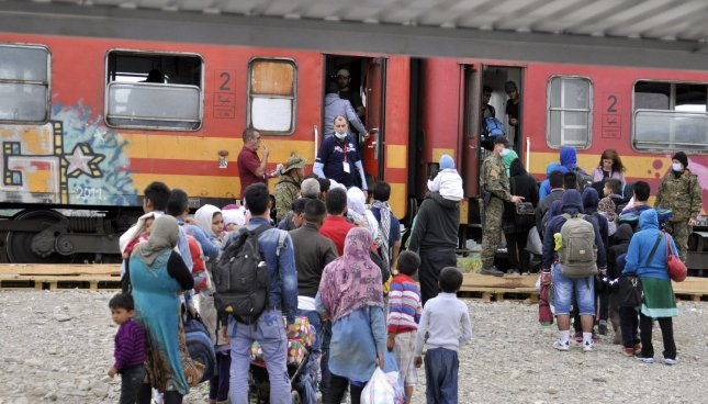 Refugees board a train in Gevgelija, Macedonia. Tensions were running high at the border after Macedonian authorities announced they would allow transit only for people from Afghanistan, Syria and Iraq. Photo by Borce Popovski/UPI