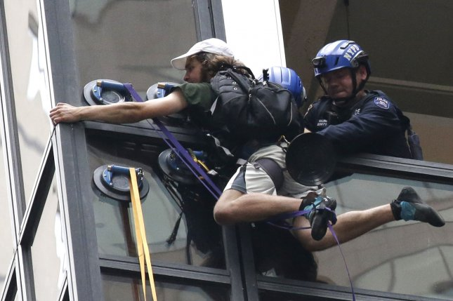 Police and rescuers pull a man, who had been scaling Trump Tower with suction cups, into the building on August 10, 2016 in New York City. The man, who police sources identified as Steve from Virginia, was grabbed by police through a busted out window pane from the 21st floor and pulled to Safety. Photo by John Angelillo/UPI