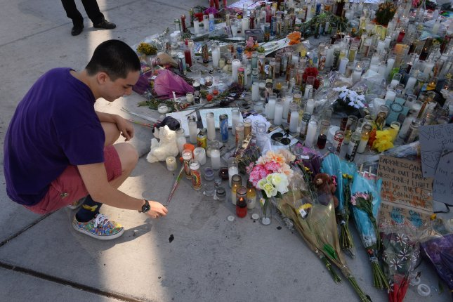 Las Vegas resident Ken Summers lights a candles at a makeshift memorial for the victims of the Las Vegas shooting on Tuesday. Photo by Jim Ruymen/UPI