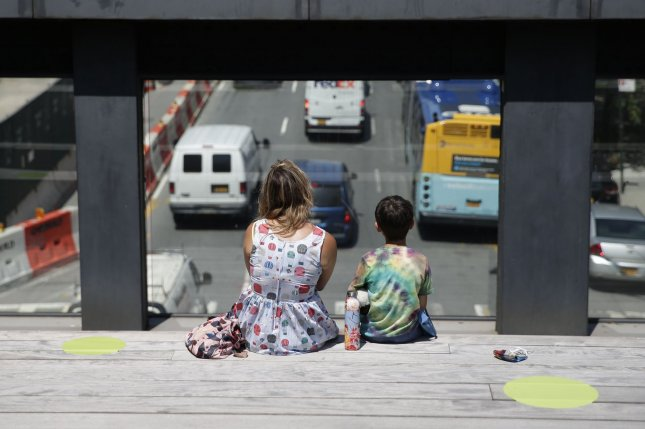 Children hospitalized with COVID-19 are just as likely to require ICU admission as hospitalized adults, a CDC analysis finds. Pictured, a woman and child sit between neon yellow circles for social distancing at The High Line park in New York City in July. Photo by John Angelillo/UPI