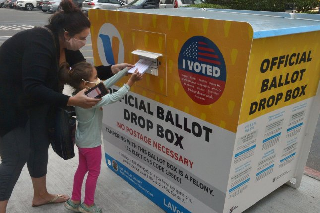 A young girl helps her mother deposit a ballot in a drop box for the 2020 general election, at the Los Angeles County Registrar in Norwalk, Calif., on October 27, 2020. File Photo by Jim Ruymen/UPI