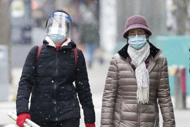 Pedestrians walk bundled up for cold weather and wearing face masks to protect from and prevent the spread of COVID-19 as snow falls in New York City in January. File Photo by John Angelillo/UPI