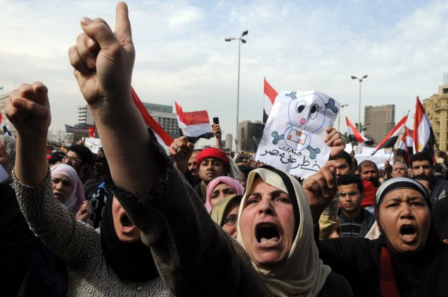 Egyptian anti-government demonstrators stand behind a barbed wire fence at Tahrir Square in Cairo in Egypt on February 6, 2011 on the 13th day of protests calling for the ouster of President Hosni Mubarak. UPI