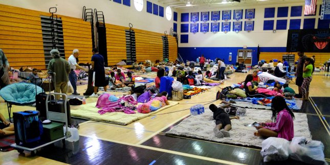Palm Beach County residents are seen getting comfortable inside of the Park Vista Hight School shelter in Boynton Beach, Fla., while waiting for the arrival of Hurricane Matthew on Thursday. Much of south Florida avoided significant damage as the storm skirted the coast overnight. Photo by Gary I Rothstein/UPI