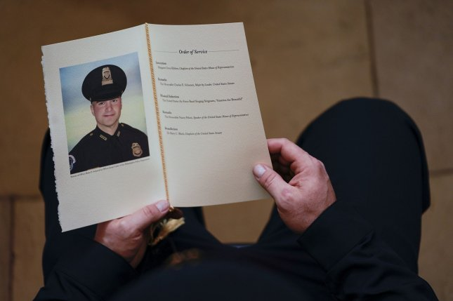 A U.S. Capitol Police Officer holds a program for the ceremony memorializing U.S. Capitol Police Officer Brian D. Sicknick, 42, as he lies in honor in the Rotunda of the Capitol on February 3. Two men were arrested in connection with an attack against Sicknick. Photo by Demetrius Freeman/UPI