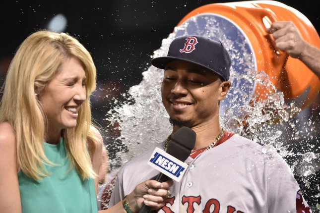 Boston Red Sox' Mookie Betts (R) is showered with water during a post-game interview with Guerin Austin. Photo by David Tulis/UPI