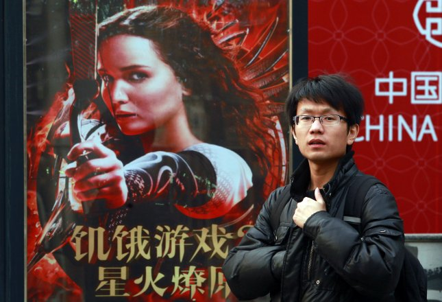 A man walks past an advertisement for the Beijing premiere of Hunger Games, a film edited to the specifications of Chinese censors. UPI/Stephen Shaver