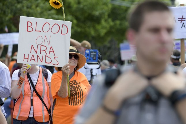 Activists march and hold signs in front of the NRA Headquarters in Fairfax, Va., on August 4, 2018. File Photo by Leigh Vogel/UPI