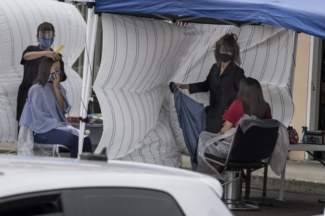 Beauticians cut patrons' hair outside at a business in Sunnyvale, Calif., on Wednesday. The state has more coronavirus cases than any other in the United States, with more than a half-million to date. Photo by Terry Schmitt/UPI