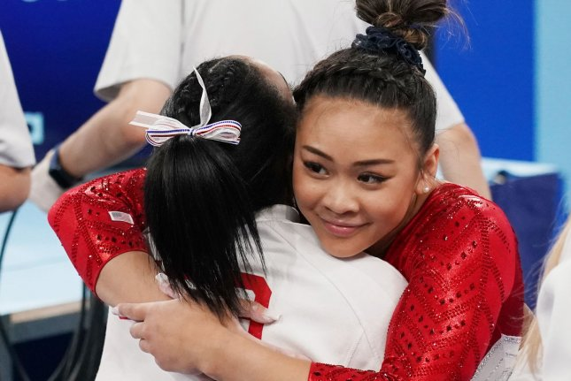 Simone Biles (L) hugs teammate Sunisa Lee after Lee's balance beam performance at the women's team finals at the 2020 Summer Games on Tuesday in Tokyo. Photo by Richard Ellis/UPI