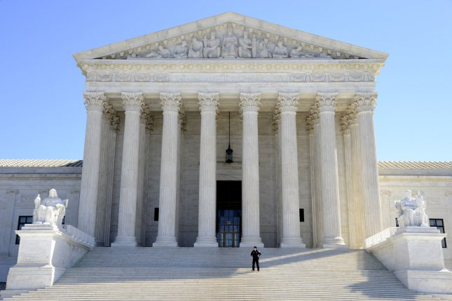 A policeman stands guard on the steps of the U.S. Supreme Court on March 29. Monday, the high court ruled unanimously that criminal courts can consider whether a defendant is already serving a mandatory minimum term when weighing punishment on another conviction. Photo by Mike Theiler/UPI