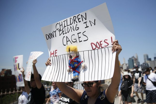 Protesters hold up signs as they walk across the Brooklyn Bridge at the End Family Separation NYC Rally and March in New York City in 2018. File Photo by John Angelillo/UPI