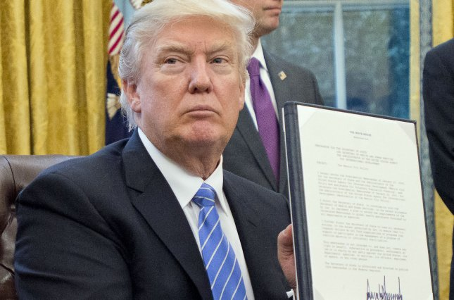 President Donald Trump holds up a presidential memorandum he signed in the Oval Office on Monday. One of the actions he signed revived the so-called global gag rule, which bars U.S. aid funds from going to U.S. non-government health groups in poor countries overseas that perform or recognize abortion as a family-planning service. Pool Photo by Ron Sachs/UPI