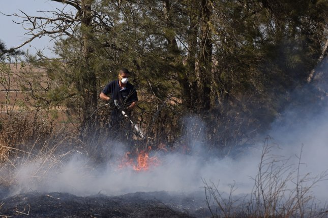 An Israeli firefighter attempts to extinguish a fire near Kibbutz Kfar Azza, along the border of the Gaza Strip, that was ignited by kites sent by Palestinian protesters in Gaza on Tuesday. Photo by Debbie Hill/UPI