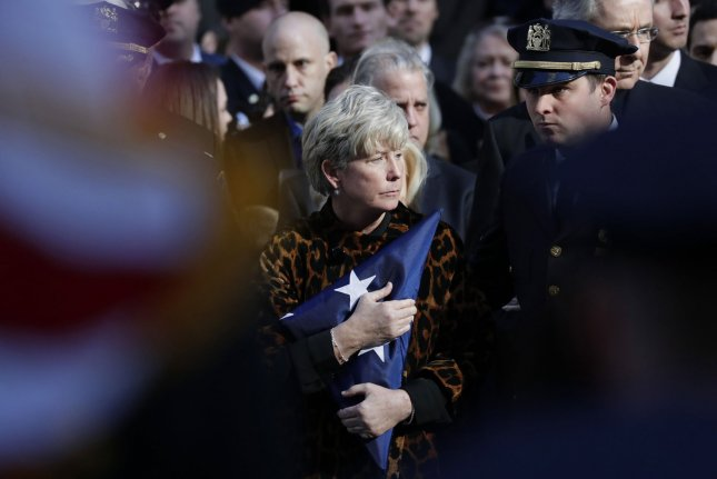 Patti Ann Mc­Donald holds a folded flag during a memorial service for NYPD Det. Steven McDonald at St. Patrick's Cathedral in New York City on Friday. McDonald, who was paralyzed after a 1986 shooting and became a symbol of strength and integrity, died Tuesday after suffering a heart attack last week. Photo by John Angelillo/UPI