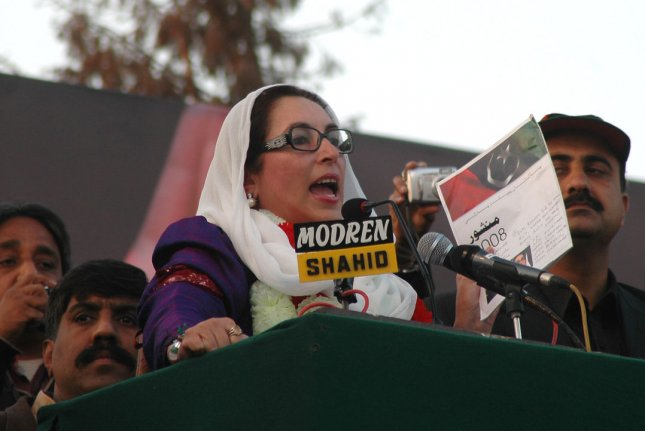 Former Pakistani Prime Minister Benazir Bhutto speaks with the watchful eye of security during an election rally in Rawalpindi on December 27, 2007. On October 18, Bhutto returned home after eight years in exile. A suicide bomber killed more than 140 people in her convoy. UPI File Photo